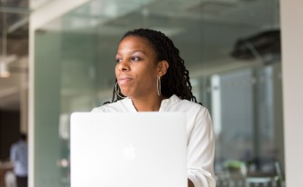 Vrouw achter laptop kijkt naar buiten.