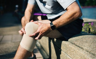 man trekt elastische knie brace aan