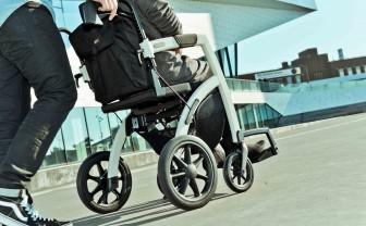 Een verzorger duwt een oudere vrouw in de Rollz Motion als rolstoel