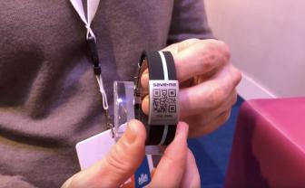 man houdt sos armband met qr code vast