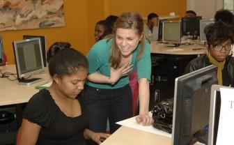 Een jongere vrouw zit achter de computer. Een andere vrouw staat bij haar tafel en helpt haar.