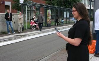 Vrouw wacht bij de bushalte met GoOV app