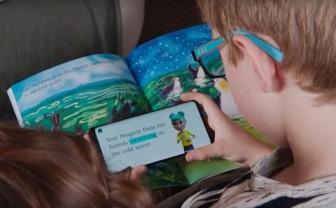 Jongen kijkt op smartphone waarop poppetje gebarentaal doet terwijl ze de woorden van een boek leest.