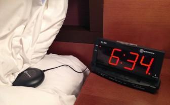 Wekker op een nachtkastje met daaraan een trilschijf die op het bed onder het kussen is geplaatst