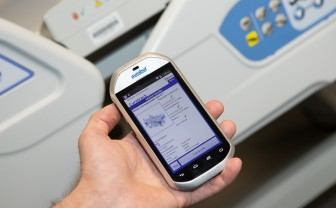 Zorgprofessional met smart phone in zijn hand waarop de app CureTrack te zien is, track and trace voor medische apparatuur