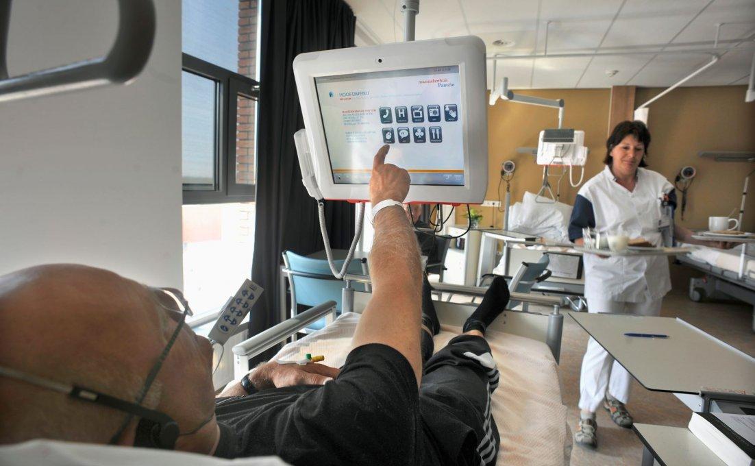 Man in ziekenhuisbed tikt iets aan op het scherm dat aan zijn bed vastzit.