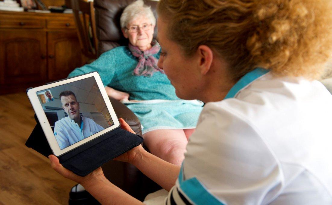 Wijkverpleegkundige raadpleegt collega via een tablet over haar cliënt.
