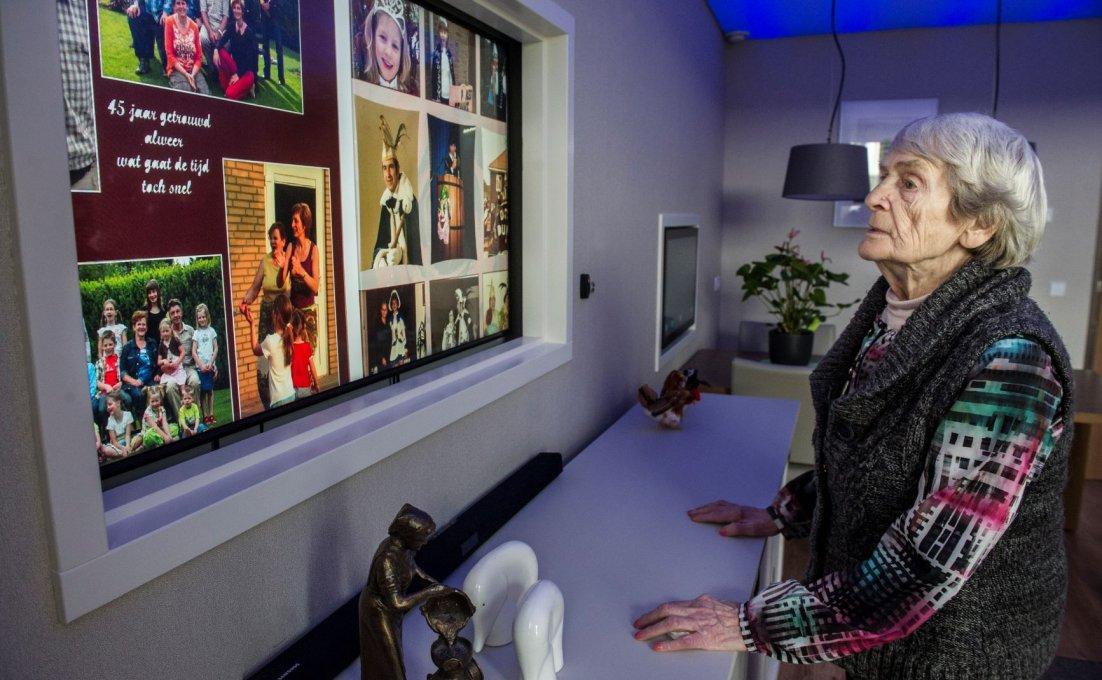 Oudere vrouw kijkt op een groot beeldscherm.