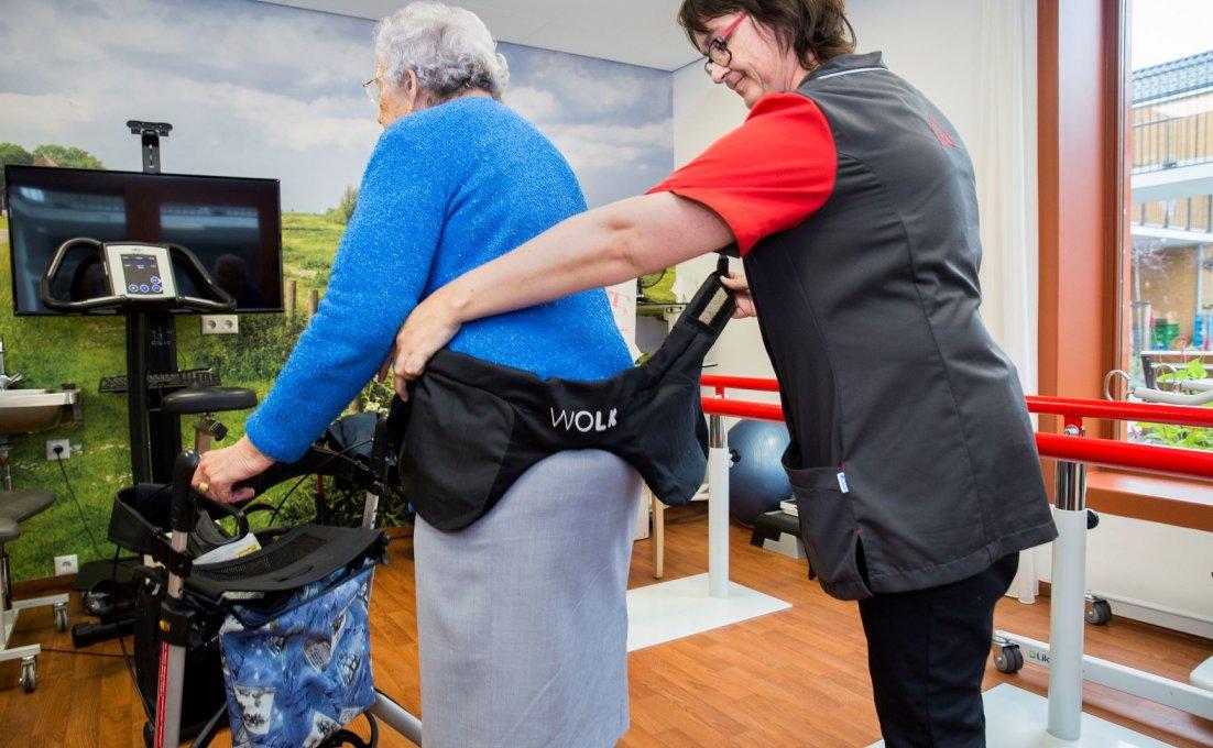 Zorgverlener helpt een oudere cliënt met een Wolk heupairbag.