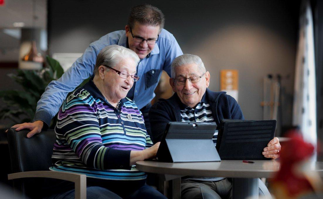 Drie ouderen kijken geamuseerd naar een tablet.