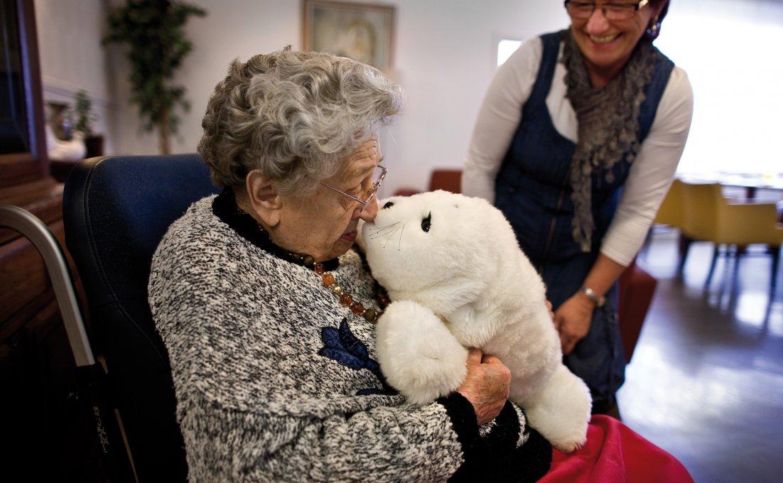 Oudere dame knuffelt met zeehondrobot Paro