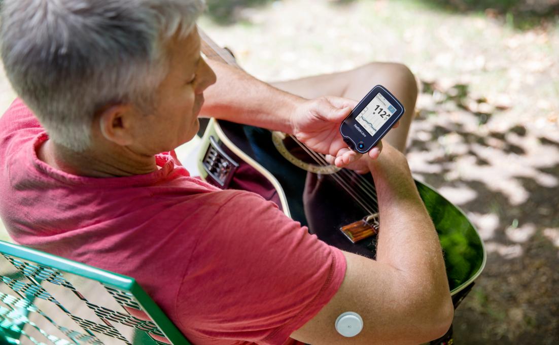 Een man heeft een sensor op zijn arm en kijkt op de app van Freestyle Libre.