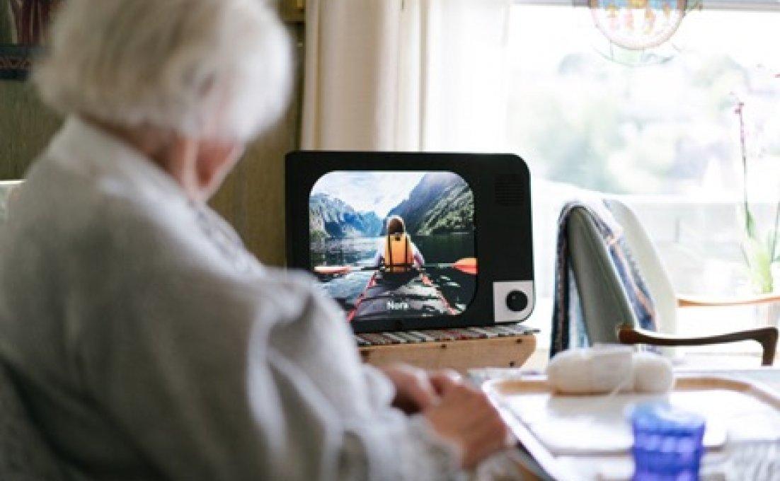 Oudere vrouw kijkt naar eenvoudige computer KOMP