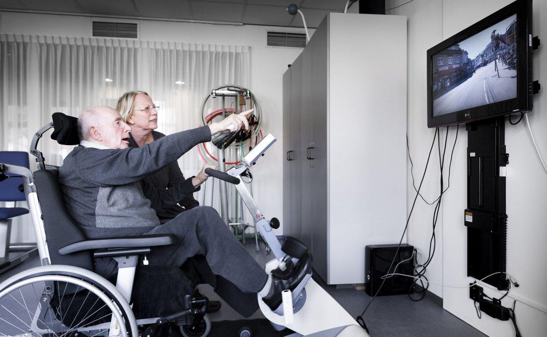 man zit in een rolstoel en fietst met zijn benen terwijl hij naar een scherm kijkt met een weg daarop.
