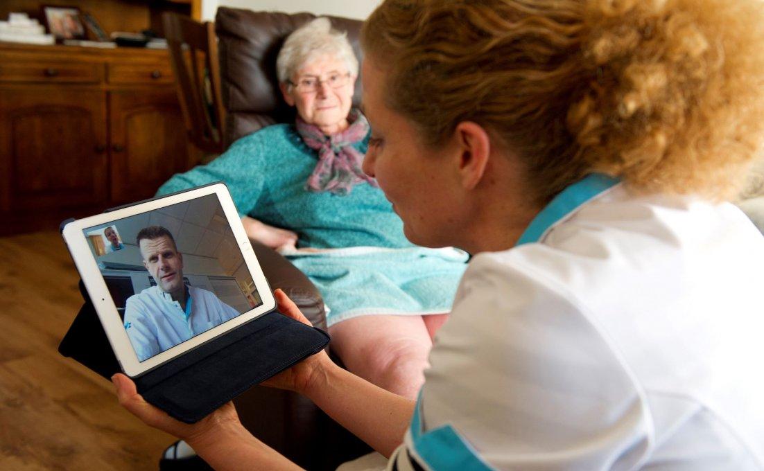 Zorgverlener bij patiënt thuis en overlegt met een collega via een tablet.