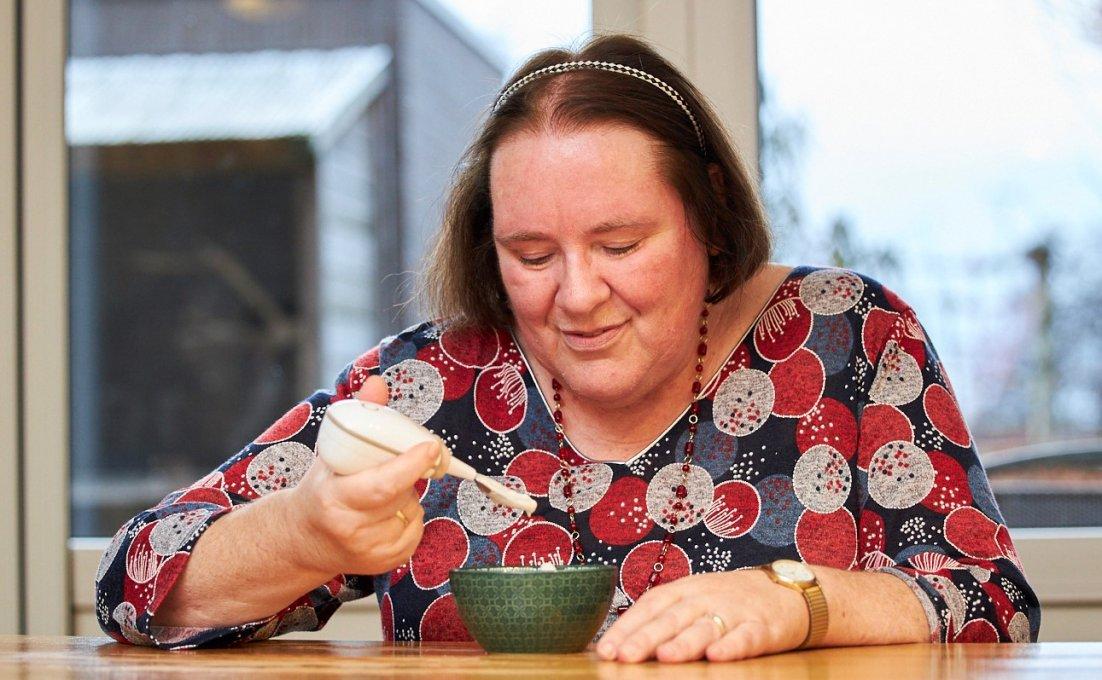 Vrouw eet met een anti tril lepel