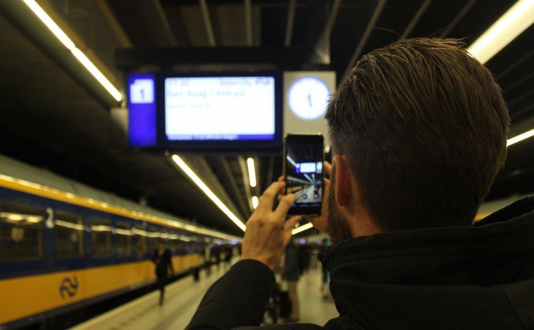 Een man op een perron richt de camera van zijn smartphone op een bord met reisinformatie van de NS.