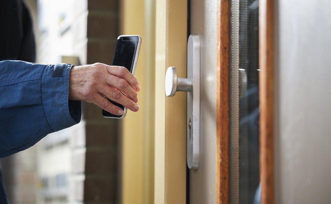 Mobiele telefoon wordt bij een slim cilinderslot gehouden