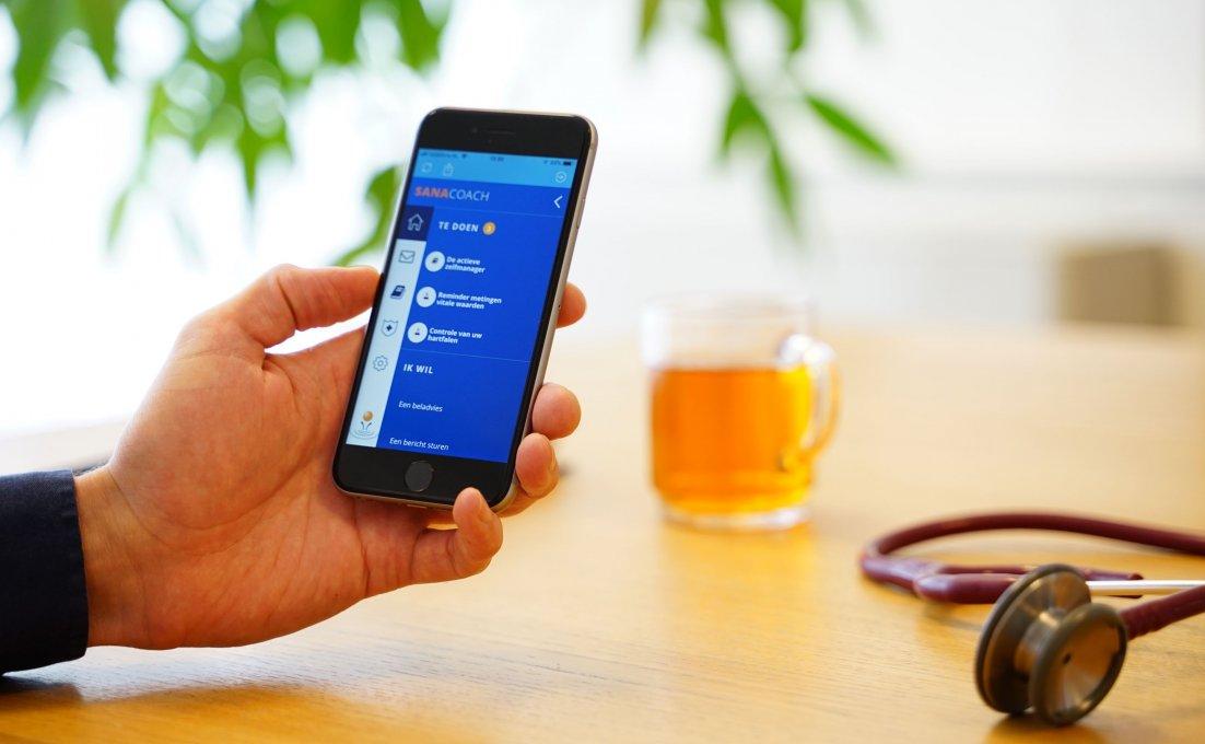 Een hand houdt een smartphone vast. Op het scherm is de app SanaCoach Astma te zien