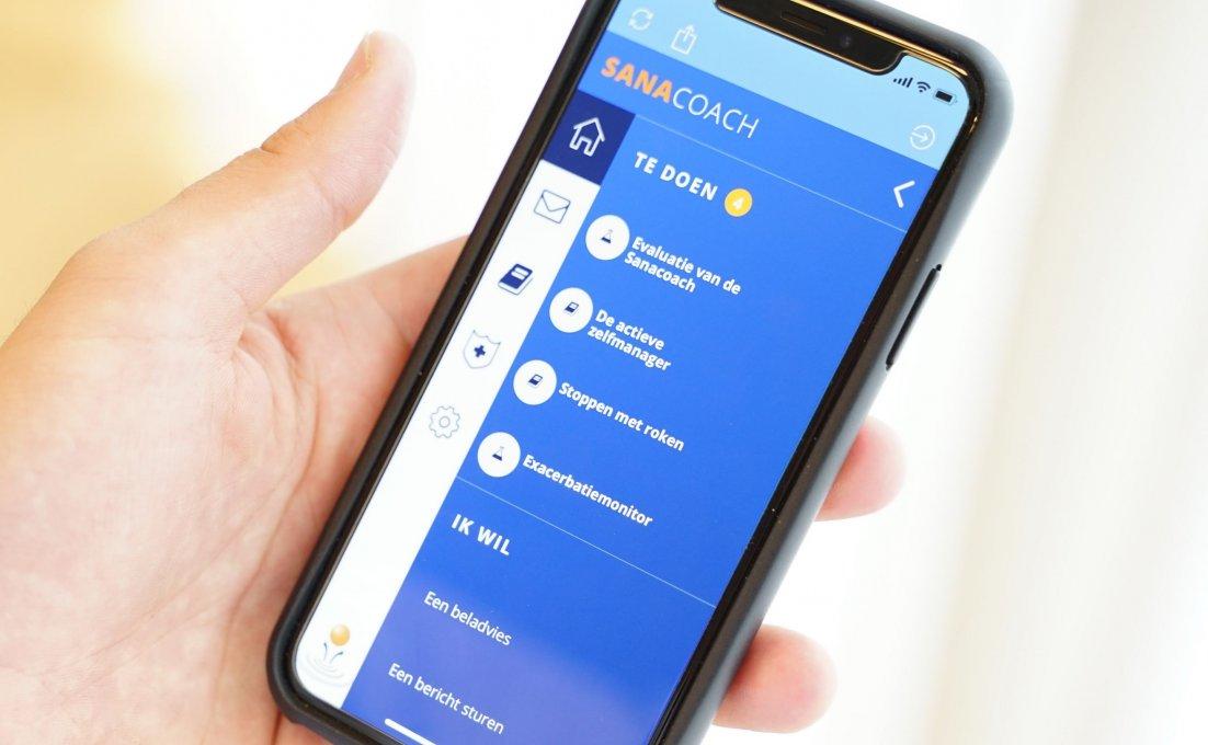 Een hand houdt een telefoon vast. Hierop is het platform SanaCoach COPD te zien.