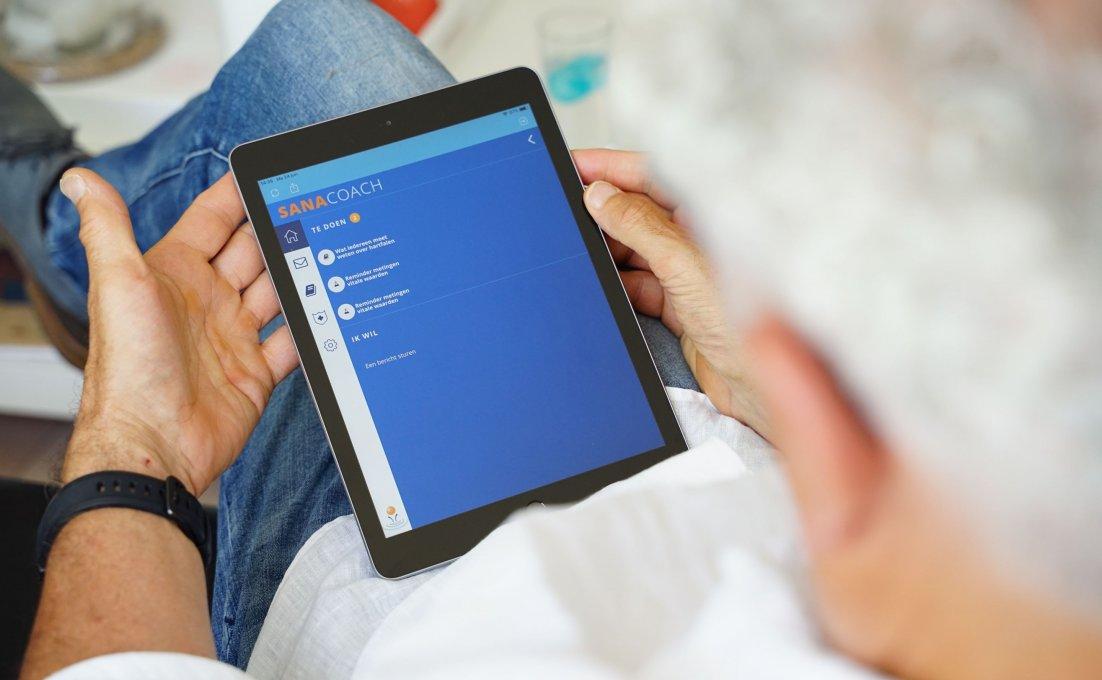 Twee handen houden een tablet vast. Hierop is het platform SanaCoach COPD te zien.