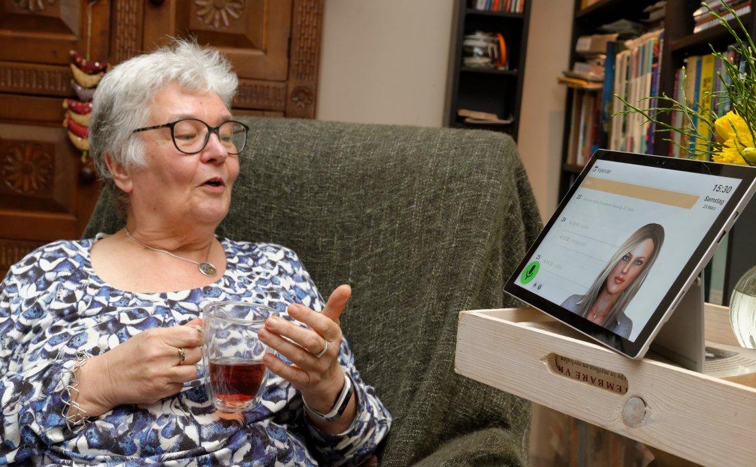 Oudere vrouw praat met virtuele assistent Anne op beeldscherm.