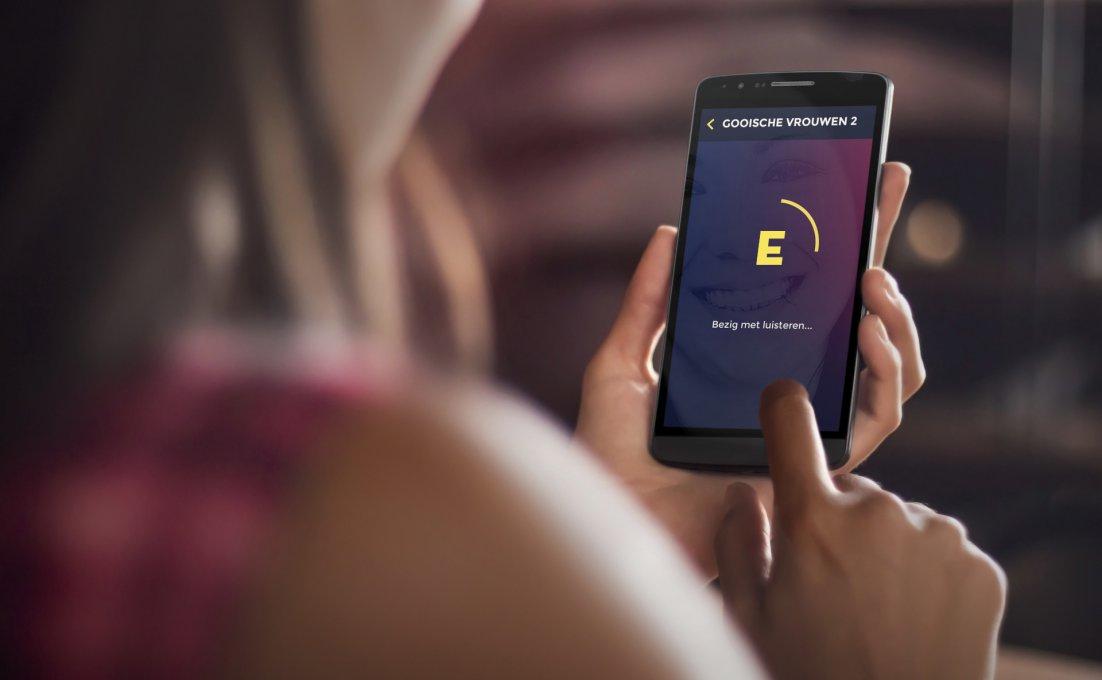 Een vrouw houdt een smartphone vast waarop de app met audiodescriptie te zien is.
