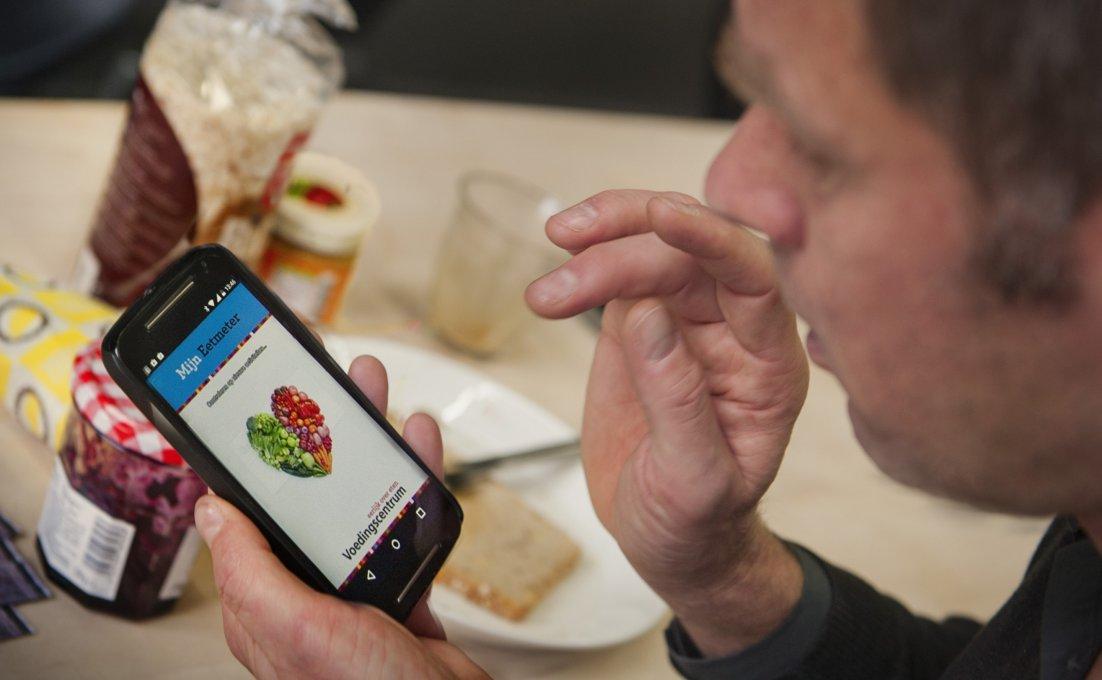 Een man zit aan tafel en gebruikt de Eetmeter app. Er staat broodbeleg op tafel en er ligt een bord met een boterham.