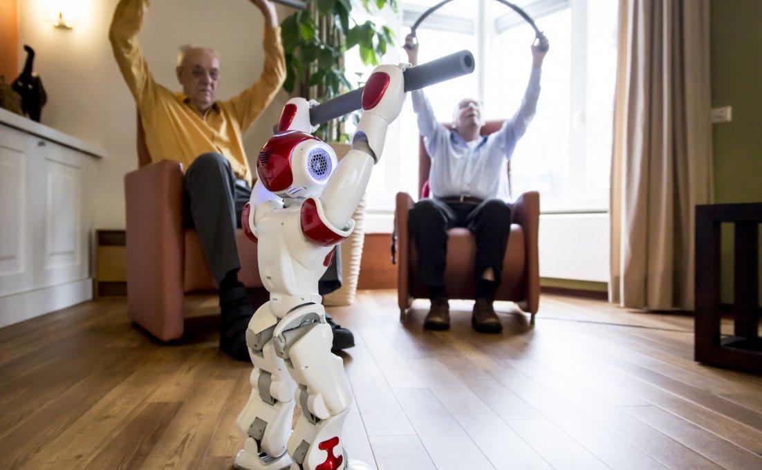 robot Zora doet oefening voor, twee ouderen op achtergrond doen het na