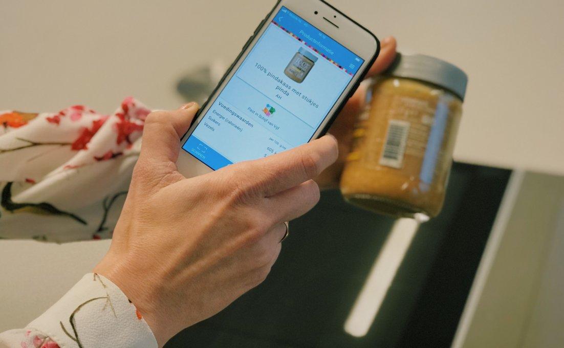 Een mevrouw scant een pot pindakaas met de app Kies ik gezond?. Op het scherm verschijnt informatie over het product