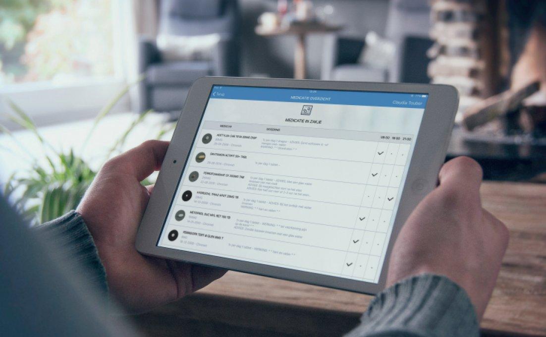 Een persoon houdt een tablet vast. Op het tablet is de app van MediCheck geopend
