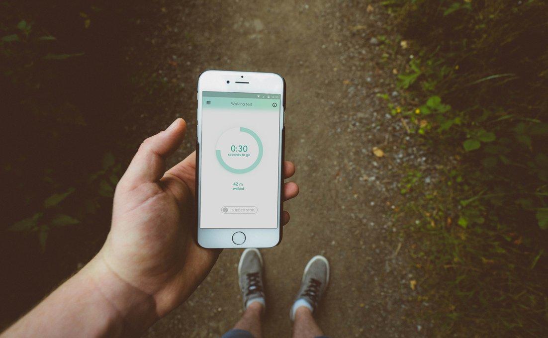 Een hand houdt een smartphone vast met daarop MS Sherpa-app
