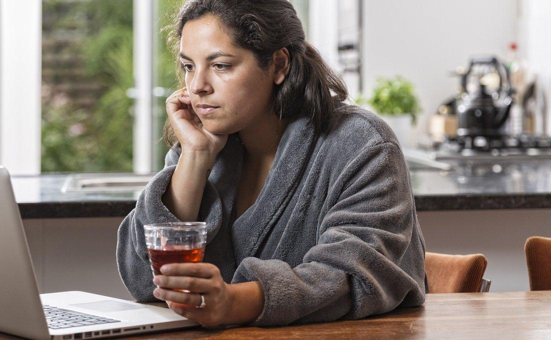 jonge vrouw zit achter haar laptop met kopje thee