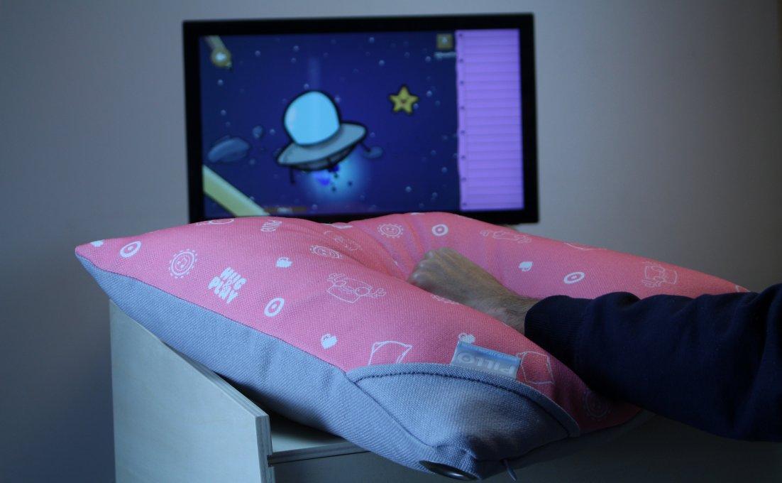 Dotty games op een beeldscherm en daarvoor een hand op het kussen Pillo