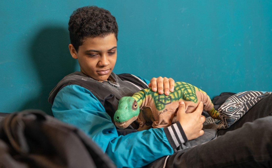 Jongen houdt Pleo dino vast.