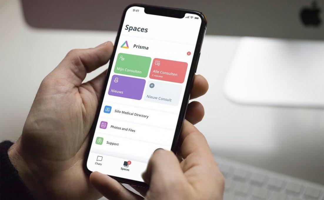Twee handen houden een smartphone vast waarop de Prisma app te zien is