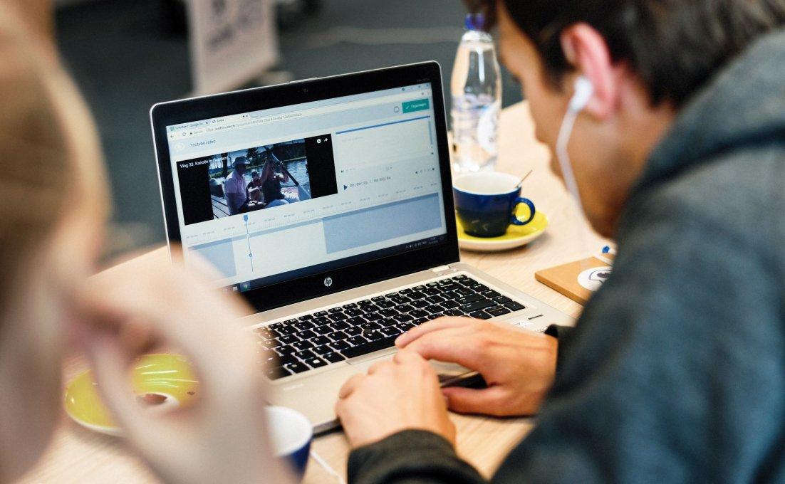 Een jongen zit achter zijn laptop en kijkt naar een filmpje met audiodescriptie