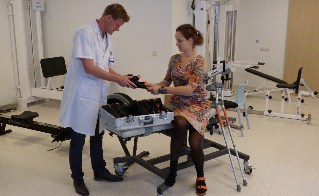 Vrouw krijgt van fysiotherapeut sandalen met sensors aan voor haar revalidatie
