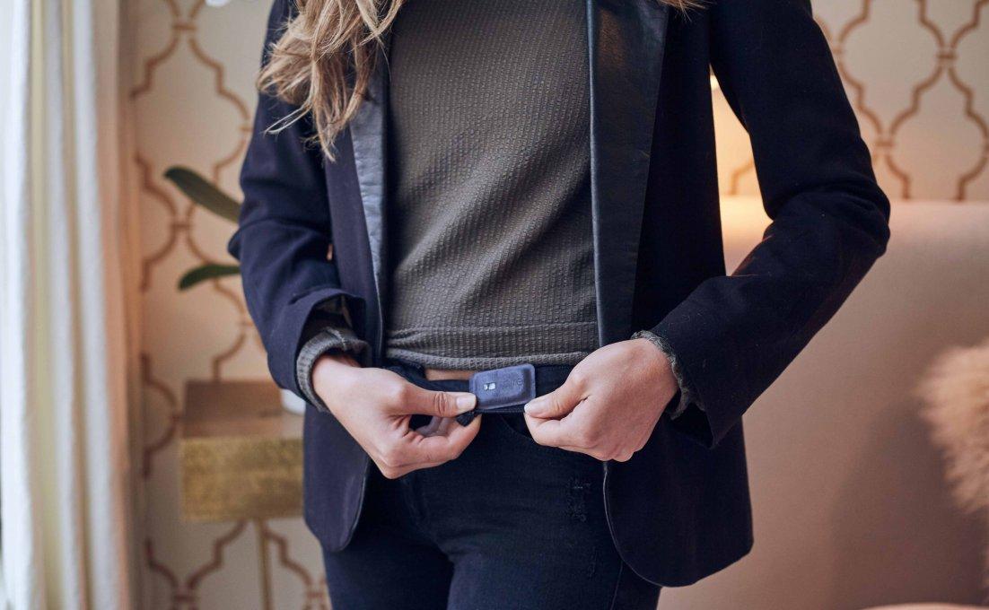 Een vrouw bevestigt de Spire Stone stressmeter aan de binnenkant van haar broek