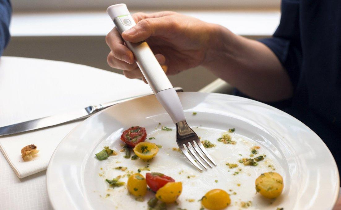 Een persoon eet een maaltijd met een trilvork. Het lampje van de trilvork is groen gekleurd. Op het bord liggen cherrytomaten..