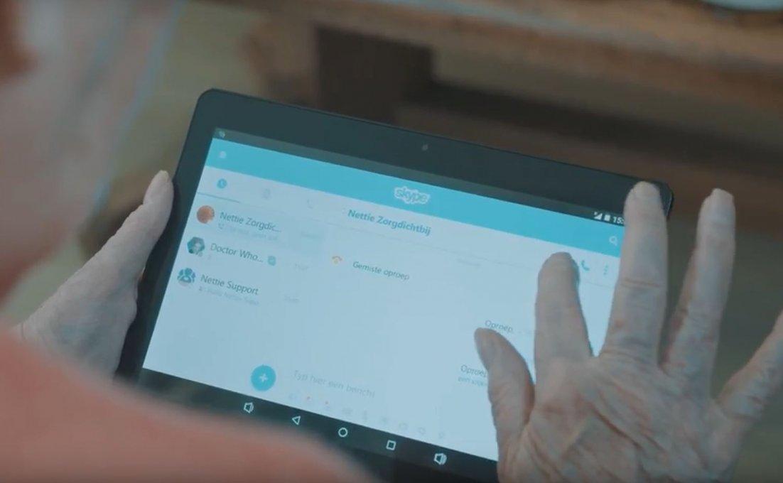 Oudere vrouw gebruikt Virtuele Thuiszorg en tikt op tabletscherm om Nettiezorg te bellen