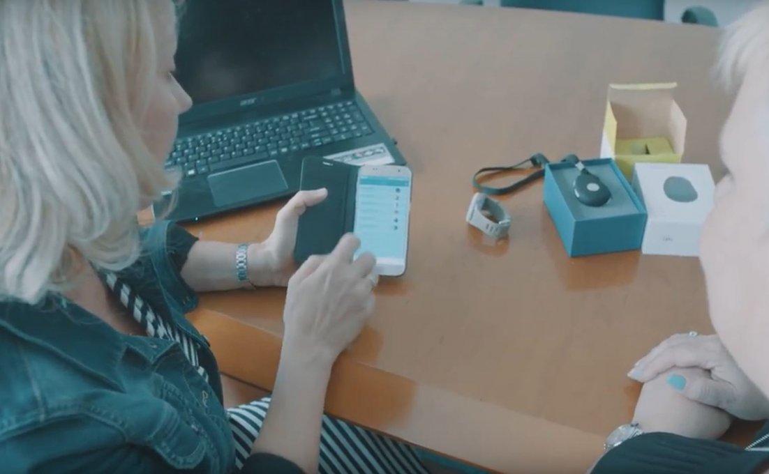 Vrouw laat de producten zien die bij virtuele thuiszorg horen, de app, de alarmering, het horloge