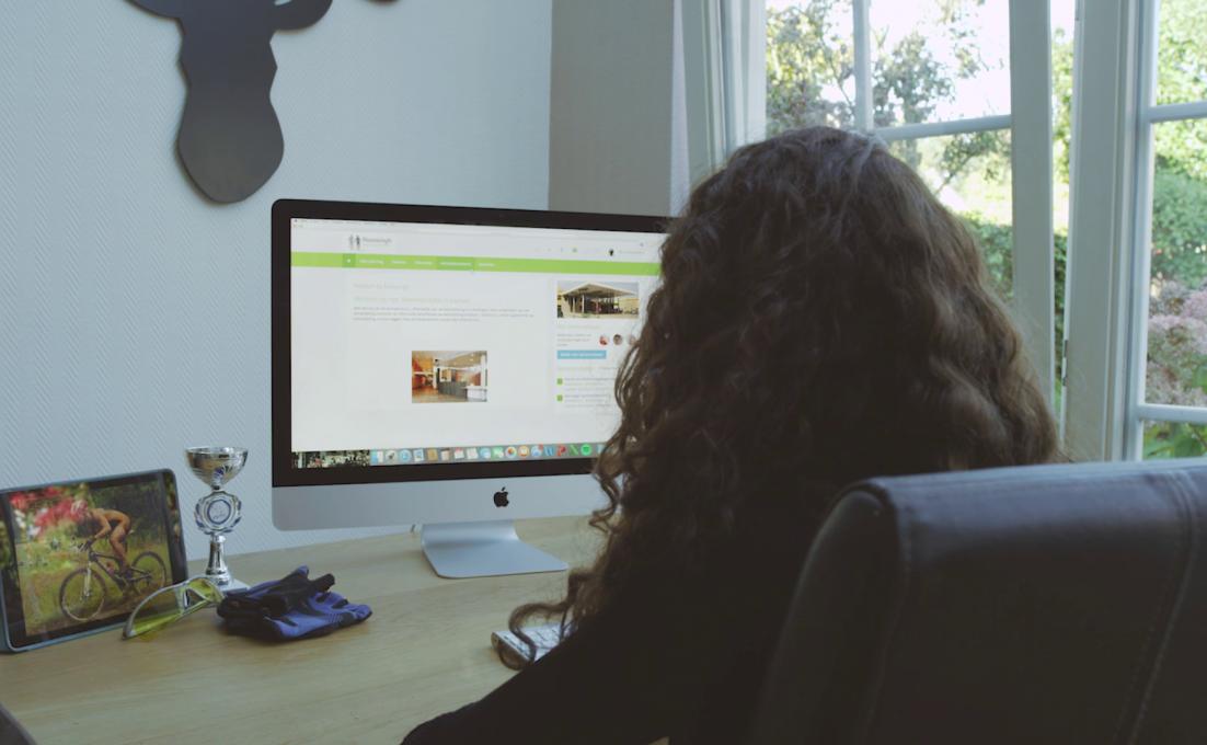 Op een stoel zit een vrouw die naar een computerscherm kijkt. Daarop is een website geopend.