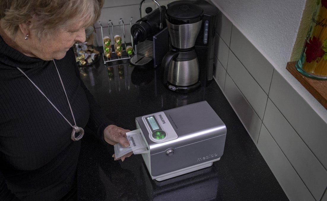 vrouw in haar keuken haalt zakje medcijnen uit medicijndispenser