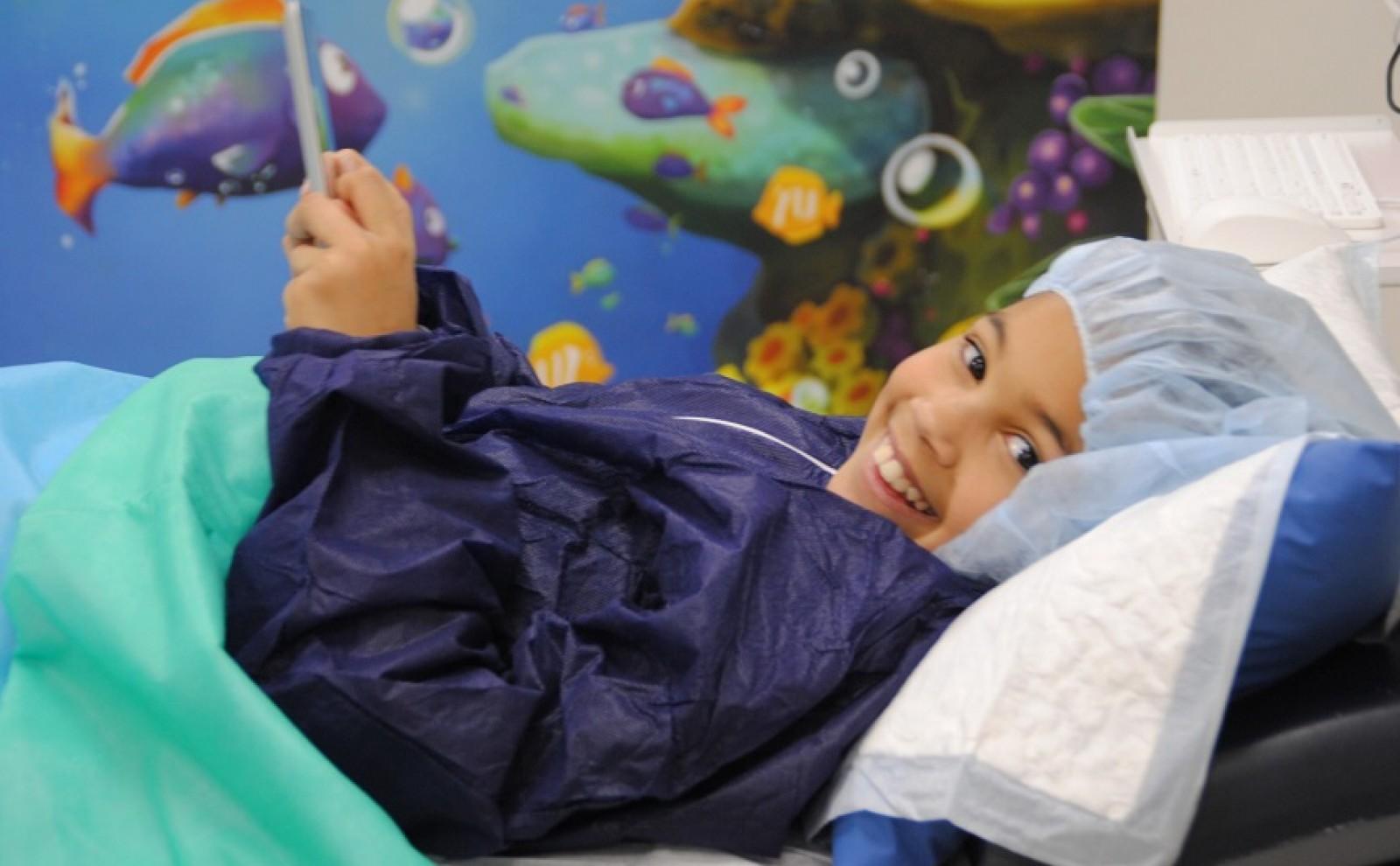 meisje ligt  met smartphone in ziekenhuisbed