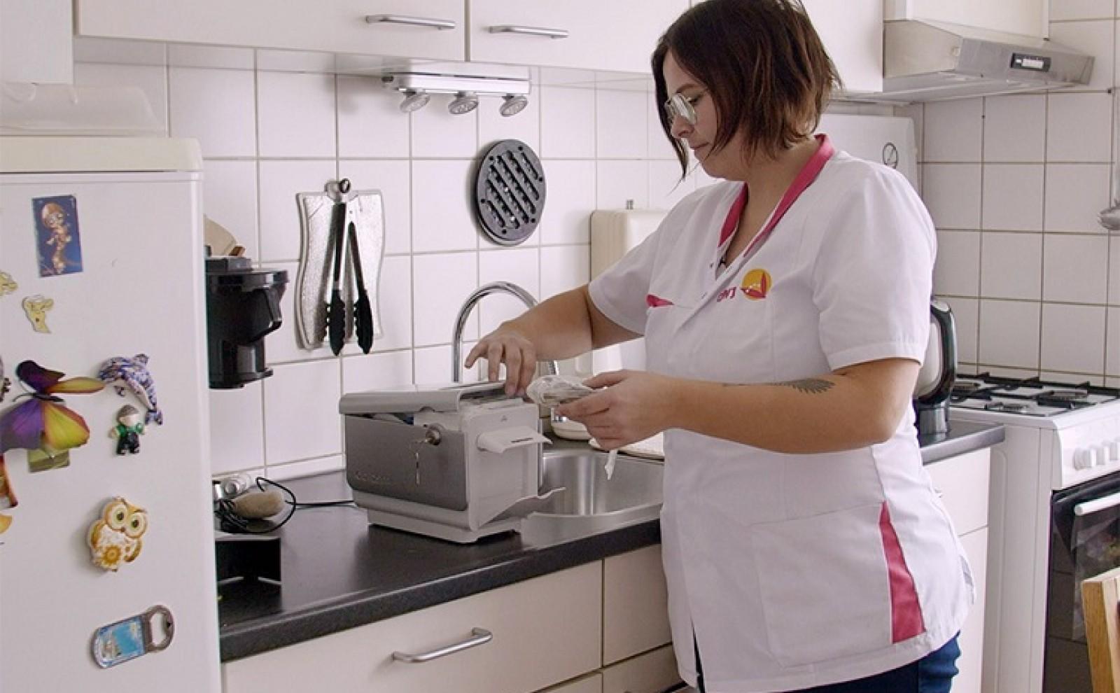 thuiszorgmedewerker vult medido slimme medicijndispenser bij