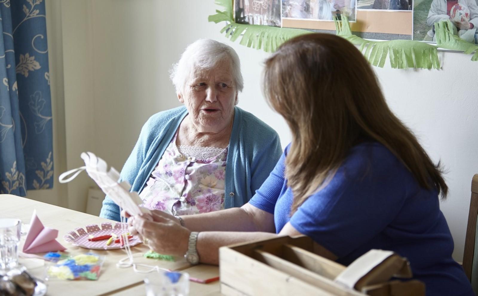 jonge vrouw helpt oudere vrouw met knutselen